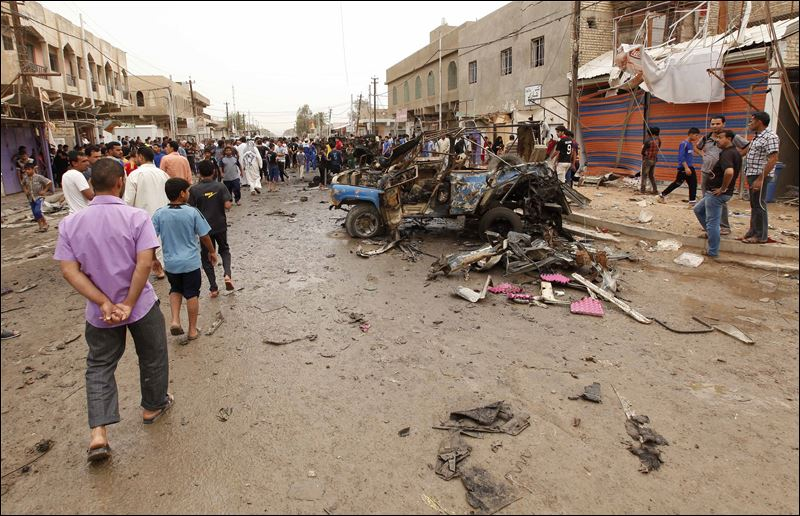 Iraqi citizens file past the scene of a car bomb attack in a Baghdad suburb in 2013.